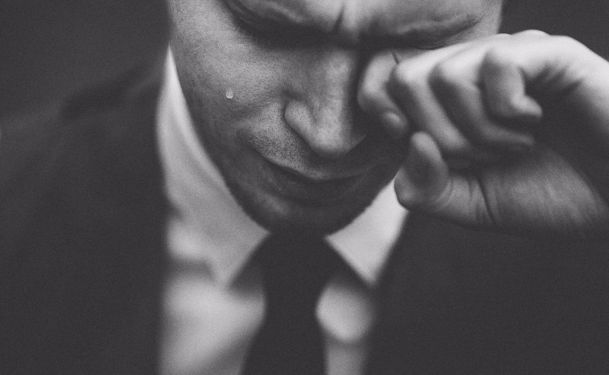 Mann i dress som gråter