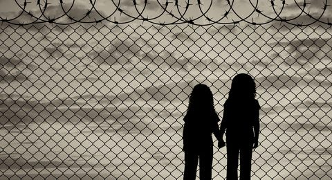 Children looking through fence a border