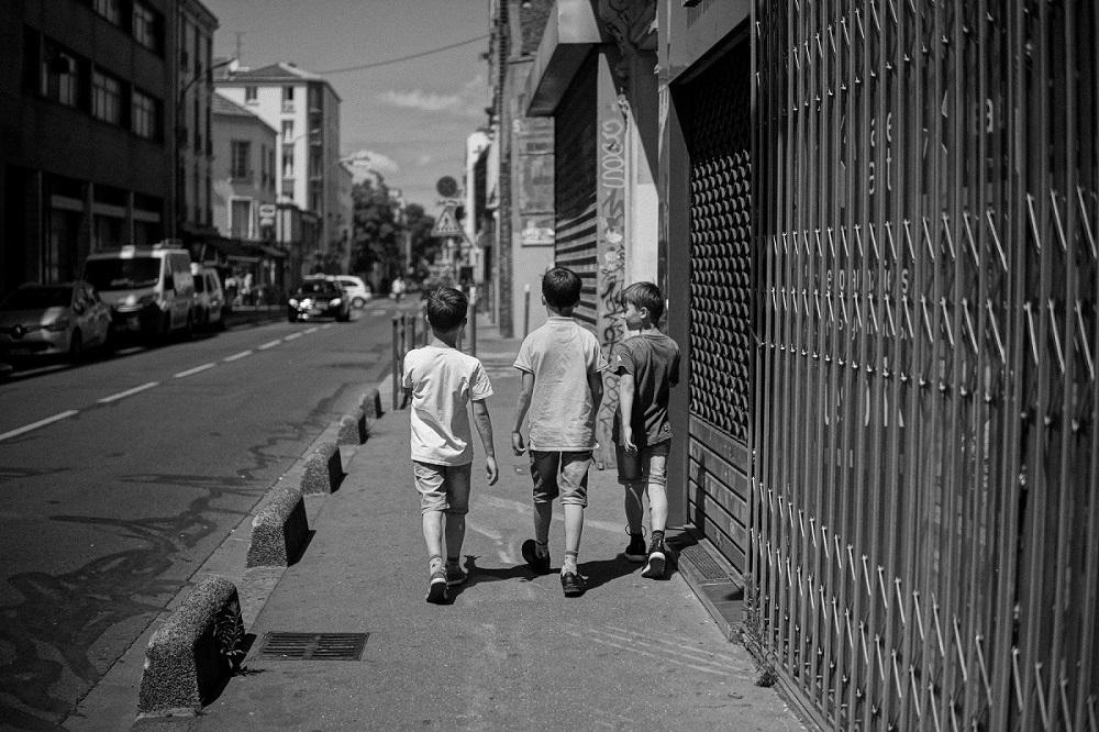 Foto av tre gutter gående nedover gaten i Paris